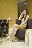 年轻女人坐在沙发上打手机