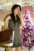 拿着购物袋打手机的年轻女人