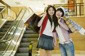 两个快乐的年轻女子拿着购物袋