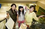 三个快乐的年轻女子拿着购物袋