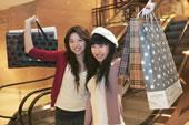 两个快乐的年轻女子举着购物袋
