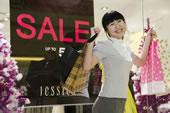 一个快乐的年轻女人举着购物袋