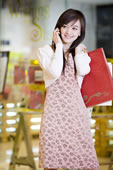 一个年轻女人拿着购物袋打手机