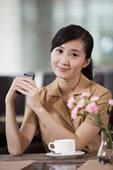 年轻商务女士在咖啡厅使用手机