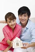 年轻情侣拿着房子模型