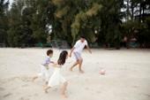 中年人和小女孩、小男孩在海边踢足球