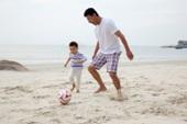 中年人和小男孩在海边踢足球