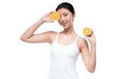 年轻女子手拿橙子