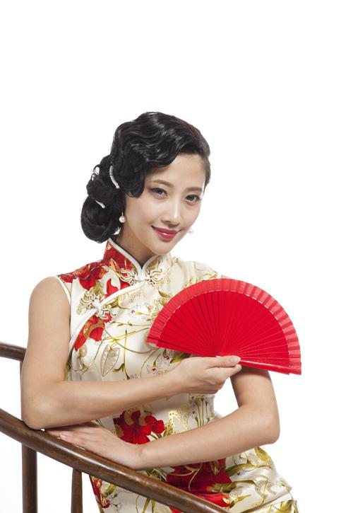 棚拍身穿旗袍的年轻女人拿红色折扇