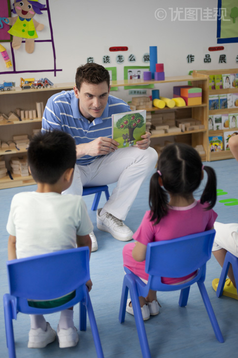 幼儿园外教男老师和小朋友们一起看画册