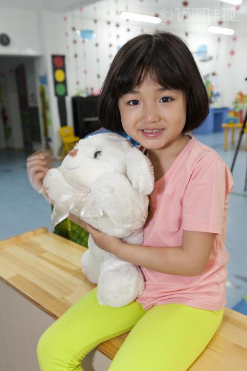 幼儿园小女孩抱着毛绒玩具